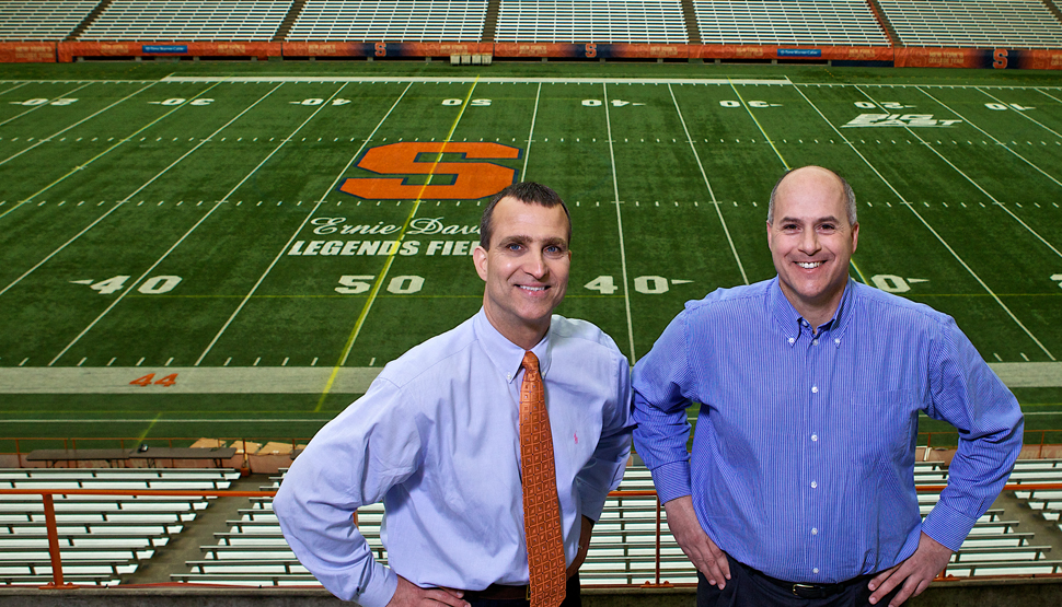 Syracuse University's risk management and associate athletic director in front of football field.